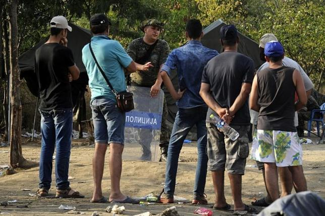 Macedonian police officer talks with migrants standing on the Greek side at the Greek-Macedonian border