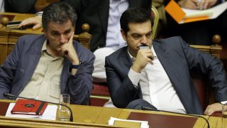 Greece's Prime Minister Alexis Tsipras, right, and Finance Minister Euclid Tsakalotos attend a parliament meeting in Athens, Thursday, July 16, 2015. Greece's Parliament has approved an austerity bill demanded by bailout creditors, despite a significant level of dissent from the governing leftist Syriza party. The bill to impose sweeping tax hikes and spending cuts was approved with the support of three pro-European opposition parties. (AP Photo/Thanassis Stavrakis)