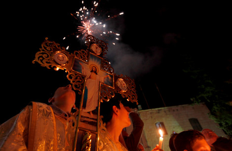 Palestinian Christians watch fireworks during the ceremony of the Holy Fire at a Greek Orthodox church in Gaza City, Sunday, May 5, 2013. Eastern Orthodox churches celebrate Easter, the resurrection of Jesus, on Sunday. (AP Photo/Hatem Moussa)