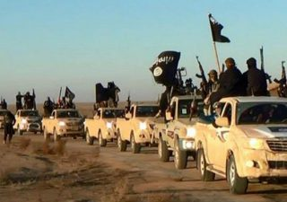 FILE - In this undated file photo released by a militant website, which has been verified and is consistent with other AP reporting, militants of the Islamic State group hold up their weapons and wave flags as they ride in a convoy, which includes multiple Toyota pickup trucks, through Raqqa city in Syria on a road leading to Iraq. Toyota is working with U.S. officials after questions were raised about the prominent use of its vehicles by militant organizations in Syria, Iraq and Libya. (Militant website via AP, File)