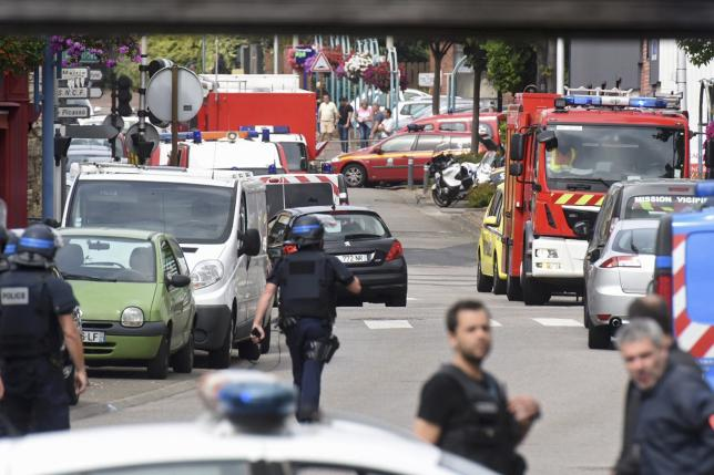 Police and rescue workers stand at the scene after two assailants had taken five people hostage in the church at Saint-Etienne-du -Rouvray near Rouen in Normandy, France, July 26, 2016.  REUTERS/Steve Bonet