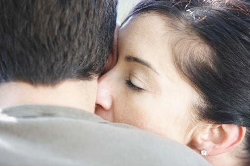 Woman kissing mans neck