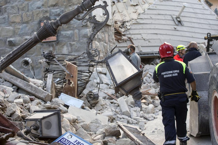 epa05508218 Members of the Protezione Civile (Civil Protection) department operate on the rubble of a collapsed building in Amatrice, central Italy, 24 August 2016, following a 6.2 magnitude earthquake, according to the United States Geological Survey (USGS), that struck at around 3:30 am local time (1:30 am GMT). The quake was felt across a broad section of central Italy, including the capital Rome where people in homes in the historic center felt a long swaying followed by aftershocks. According to reports at least 21 people died in the quake, 11 in Lazio and 10 in Marche regions.  EPA/MASSIMO PERCOSSI