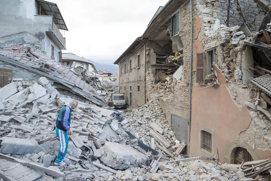 epa05508228 A man walks on the rubble of collapsed buildings in Amatrice, central Italy, 24 August 2016, following a 6.2 magnitude earthquake, according to the United States Geological Survey (USGS), that struck at around 3:30 am local time (1:30 am GMT). The quake was felt across a broad section of central Italy, including the capital Rome where people in homes in the historic center felt a long swaying followed by aftershocks. According to reports at least 21 people died in the quake, 11 in Lazio and 10 in Marche regions.  EPA/MASSIMO PERCOSSI
