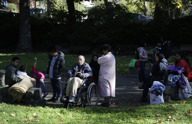 People sit outside in a town park in Norcia, central Italy, after an earthquake with a preliminary magnitude of 6.6 struck central Italy, Sunday, Oct. 30, 2016. A powerful earthquake rocked the same area of central and southern Italy hit by quake in August and a pair of aftershocks last week, sending already quake-damaged buildings crumbling after a week of temblors that have left thousands homeless.  (AP Photo/Gregorio Borgia)