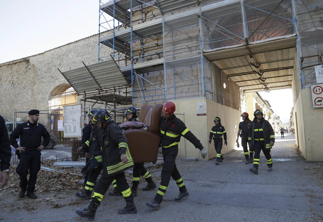 Italian firefighters carry an armchair from the historical center of Norcia, central Italy, which has been sealed off, after an earthquake with a preliminary magnitude of 6.6 struck central Italy, Sunday, Oct. 30, 2016. A powerful earthquake rocked the same area of central and southern Italy hit by quake in August and a pair of aftershocks last week, sending already quake-damaged buildings crumbling after a week of temblors that have left thousands homeless.  (AP Photo/Gregorio Borgia)