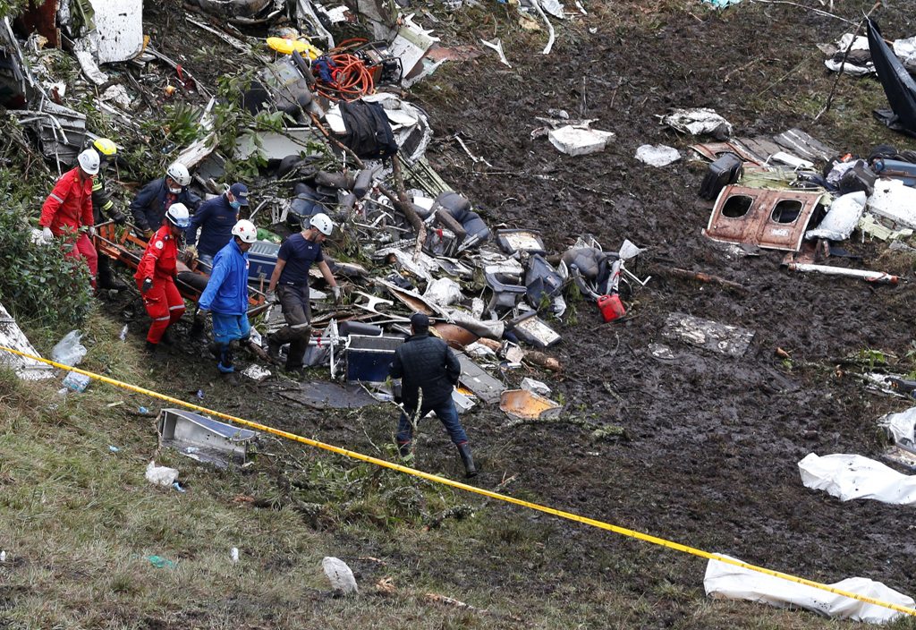 Rescue workers carry the body of a victim from a plane that crashed into the Colombian jungle with Brazilian soccer team Chapecoense onboard, near Medellin