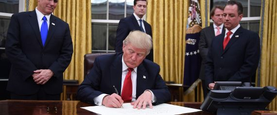 US President Donald Trump signs an executive order as Vice President Mike Pence and Chief of Staff Reince Priebus look on at the White House in Washington, DC on January 20, 2017. / AFP / JIM WATSON        (Photo credit should read JIM WATSON/AFP/Getty Images)