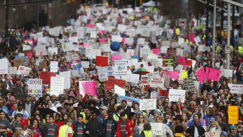 Demonstrators march Saturday, Jan. 21, 2017, in Atlanta. Thousands of people marched through Atlanta one day after President Donald Trump's inauguration. (AP Photo/John Bazemore)