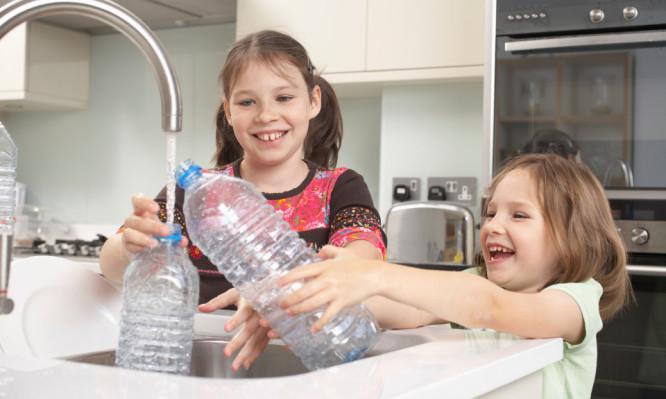 Girls filling up water bottle in kitchen