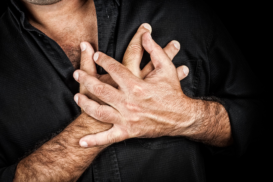 Close up of two hands grabbing a chest on a black background, useful to represent a heart attack or any sentimental concept