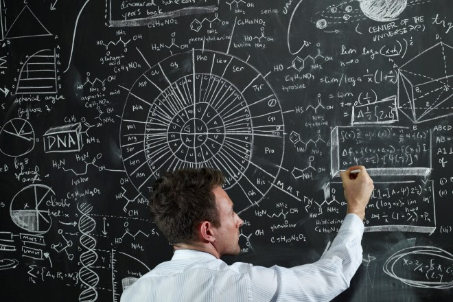 teacher writing equations on the black board