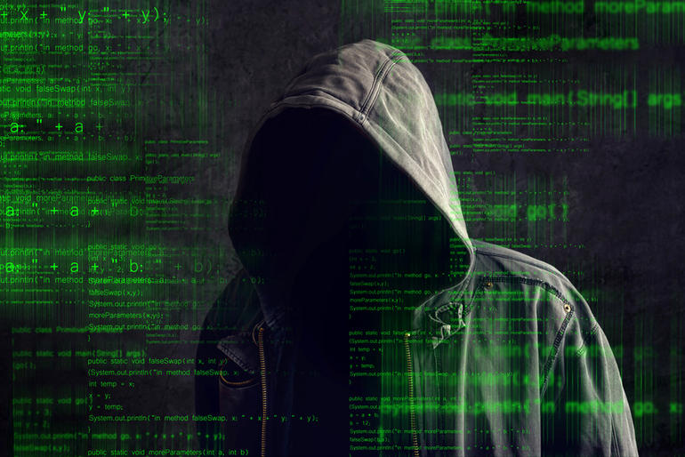 Faceless hooded anonymous computer hacker with programming code from monitor, dark web concept