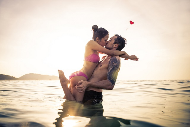 Couple of lovers kissing into water at sunset - Romantic scene of multiethnic couple