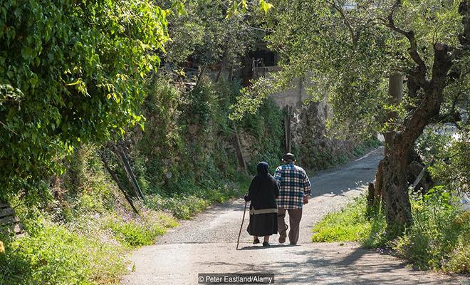 ER2CXB Elderly Greek couple walking in a country lane, Exohori village, Outer Mani, Peloponnese, Greece