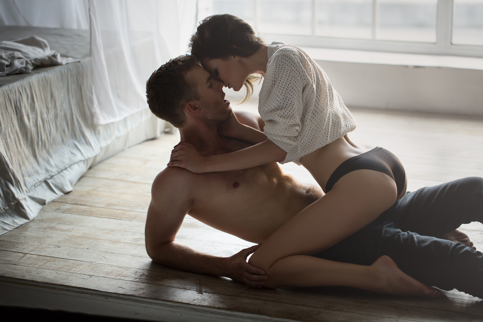 Passionate couple kissing, boy and girl sitting on wooden floor near the rumpled bed opposite the window.
