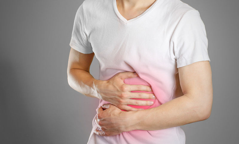 bigstock-A-Man-Holds-The-Stomach-The-P-185588926