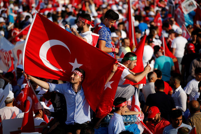 People wave Turkey's national flags as they arrive to attend a ceremony marking the first anniversary of the attempted coup at the Bosphorus Bridge in Istanbul, Turkey July 15, 2017. REUTERS/Murad Sezer