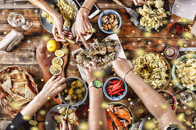 Christmas dinner. Falling golden snowflakes. Cheers Top of view of a nicely served wooden table Christmas dinner with tasty dishes and snacks friends are toasting with glasses of red and white wine. top veiw