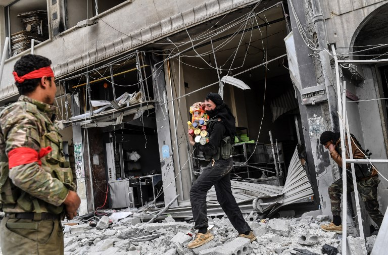 Turkish-backed Syrian rebels loot shops after seizing control of the northwestern Syrian city of Afrin from the Kurdish People's Protection Units (YPG) on March 18, 2018. In a major victory for Ankara's two-month operation against the Kurdish People's Protection Units (YPG) in northern Syria, Turkish-led forces pushed into Afrin apparently unopposed, taking up positions across the city. / AFP PHOTO / BULENT KILIC