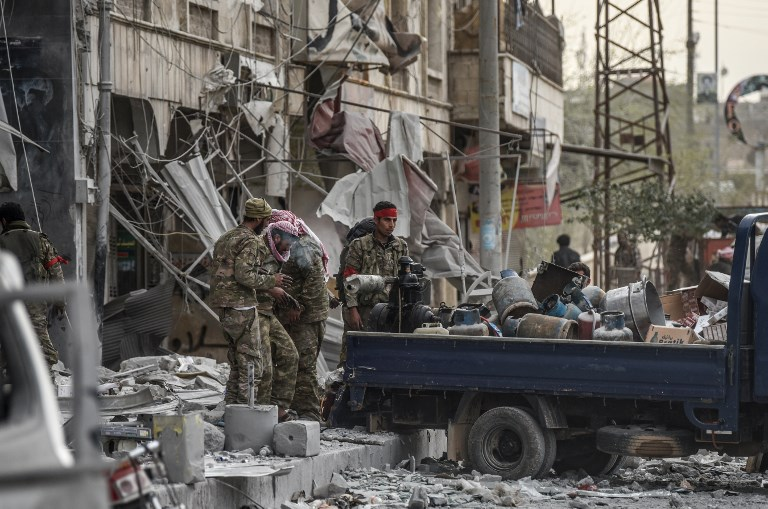 Turkish-backed Syrian Arab fighters loot shops after seizing control of the northwestern Syrian city of Afrin from the Kurdish People's Protection Units (YPG) on March 18, 2018. In a major victory for Ankara's two-month operation against the Kurdish People's Protection Units (YPG) in northern Syria, Turkish-led forces pushed into Afrin apparently unopposed, taking up positions across the city. / AFP PHOTO / BULENT KILIC