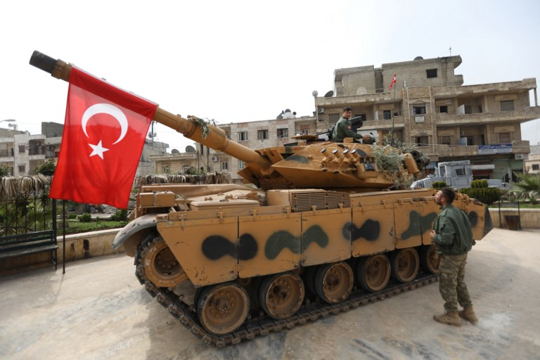 A tank belonging to Turkish soldiers and Ankara-backed Syrian Arab fighters is seen in the Kurdish-majority city of Afrin in northwestern Syria after they took control of it from Kurdish People's Protection Units (YPG) on March 18, 2018. Turkish-backed rebels have seized the centre of Afrin city in northern Syria, Ankara said, as they made rapid gains in their campaign against Kurdish forces. A civilian inside Afrin said that rebels had deployed in the city centre and that the Kurdish People's Protection Units (YPG) militia had withdrawn. / AFP PHOTO / OMAR HAJ KADOUR
