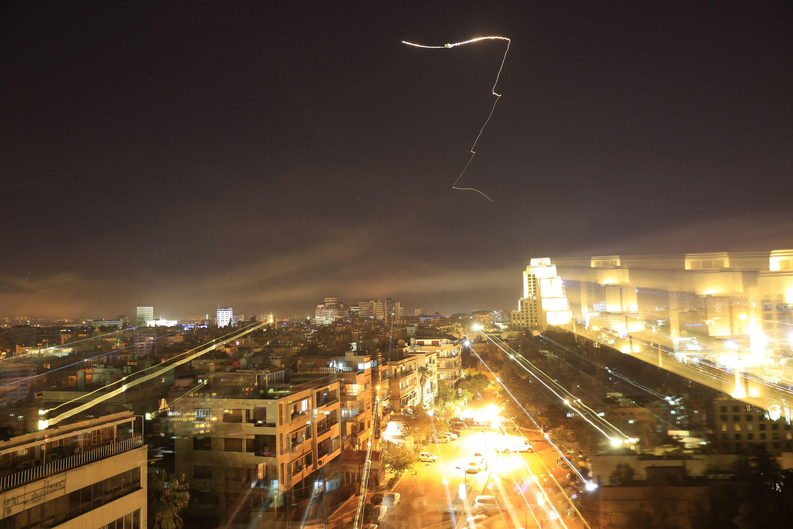 Damascus is seen as the U.S. launches an attack on Syria targeting different parts of the capital early Saturday, April 14, 2018. Syria's capital has been rocked by loud explosions that lit up the sky with heavy smoke as U.S. President Donald Trump announced airstrikes in retaliation for the country's alleged use of chemical weapons. (AP Photo/Hassan Ammar)