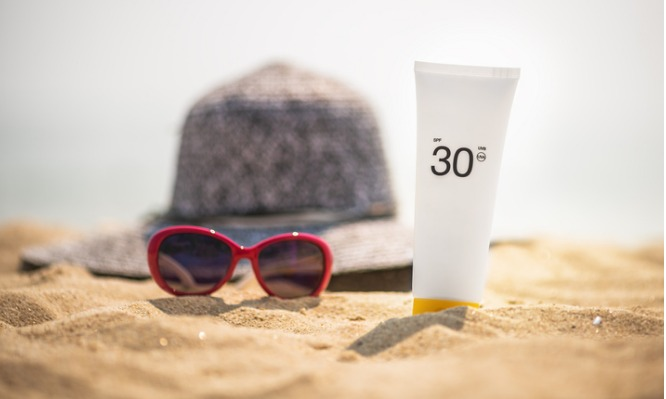 bottle-of-sunscreen-lotion-on-the-sandy-beach-picture-id678838540