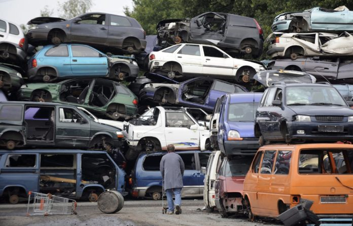 epa01844965 A customer walks along high piled scrap cars in Hamburg, Germany, 02 September 2009. Scarcely eight months after the introduction of the bonus, the sum of five billion Euros is spent, notified the Federal Office of Economics and Export Control (Bafa).  EPA/MARCUS BRANDT