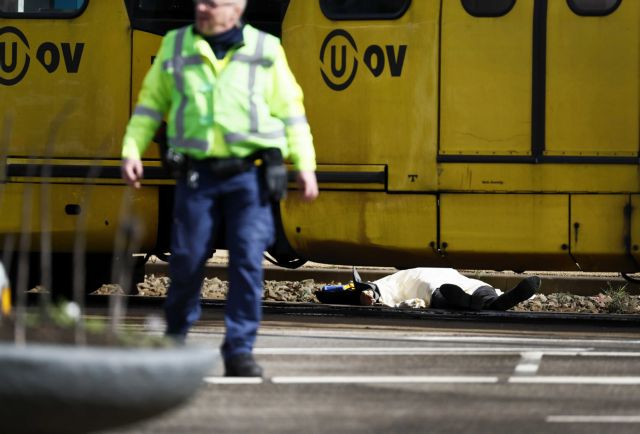 epa07446521 Armed police and a body (R) at the scene where a shooting took place at the 24 Oktoberplace in Utrecht, The Netherlands, 18 March 2019. According to the the Dutch Police, several people have been injured in a shooting on a tram in the central Dutch city of Utrecht.  EPA/ROBIN VAN LONKHUIJSEN  ATTENTION EDITORS: PICTURE CONTAINS GRAPHIC CONTENT
