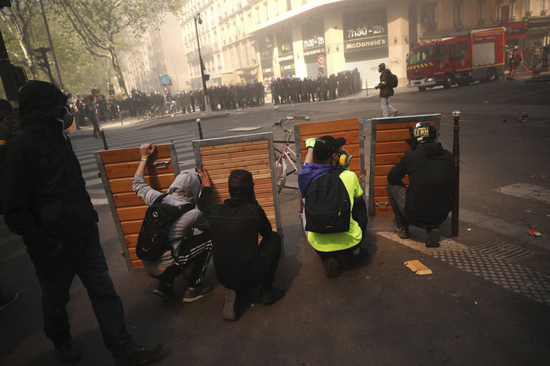 Protestos take shelter behind wooden panels during a yellow vest demonstration in Paris, Saturday, April 20, 2019. French yellow vest protesters are marching anew to remind the government that rebuilding the fire-ravaged Notre Dame Cathedral isn't the only problem the nation needs to solve. (AP Photo/Francisco Seco)