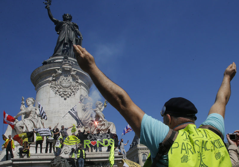 A protestor puts his arms in the air at the Place de Republique during a yellow vest demonstration in Paris, Saturday, April 20, 2019. French yellow vest protesters are marching anew to remind the government that rebuilding the fire-ravaged Notre Dame Cathedral isn't the only problem the nation needs to solve. (AP Photo/Michel Euler)