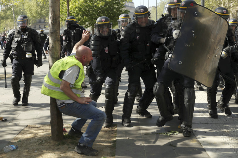 Police confront a protestor during a yellow vest demonstration in Paris, Saturday, April 20, 2019. French yellow vest protesters are marching anew to remind the government that rebuilding the fire-ravaged Notre Dame Cathedral isn't the only problem the nation needs to solve. (AP Photo/Francisco Seco)