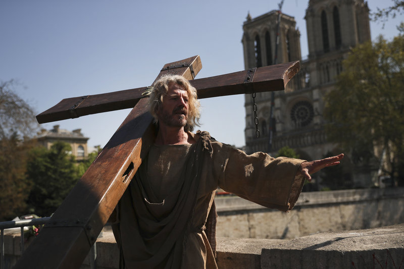 A man carries a wooden cross outside the Notre Dame Cathedral as part of a demonstration in Paris, Saturday, April 20, 2019. French yellow vest protesters are marching anew to remind the government that rebuilding the fire-ravaged Notre Dame Cathedral isn't the only problem the nation needs to solve. (AP Photo/Francisco Seco)