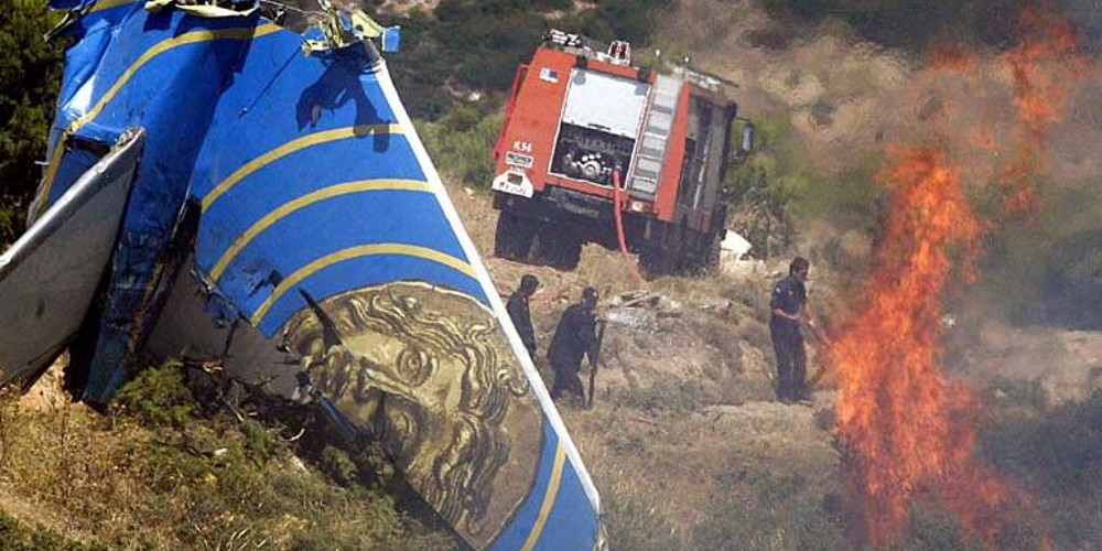 (FILES) Firemen extinguish the fire burning near the tail fin of the Cypriot passenger plane, Helios airways carrying 115 passengers and 6 crew which crashed into the mountains near Grammatiko some 45 km of Athens, on August 14, 2005. A Cyprus court on February  18, 2013 dropped manslaughter charges against budget carrier Helios Airways and four of its officials, over a 2005 crash in Greece that killed all 121 people on board, state media reported. AFP PHOTO/Louisa Gouliamaki