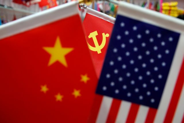 The flags of China, U.S. and the Chinese Communist Party are displayed in a flag stall at the Yiwu Wholesale Market in Yiwu, Zhejiang province, China, May 10, 2019. REUTERS/Aly Song