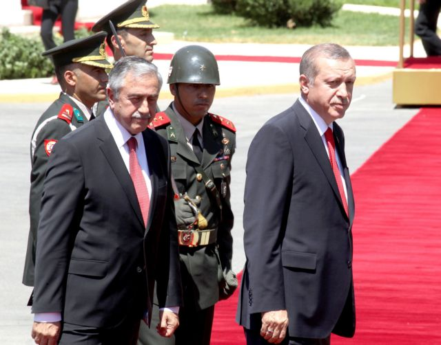 epa04854767 Turkish President Recep Tayyip Erdogan (R) reviews a military guard of honor with Turkish Cypriot leader Mustafa Akinci (L) in the Turkish occupied area of Nicosia, Cyprus, 20 July 2015. The parade was part of the celebrations marking the 41st anniversary of the invasion and occupation of the northern part of the island.  EPA/STRINGER