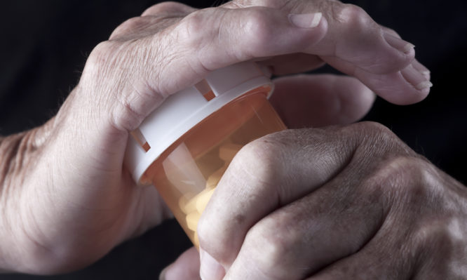 Selective-focus image of Arthritic/Senior Adult Hands opening a pill bottle
