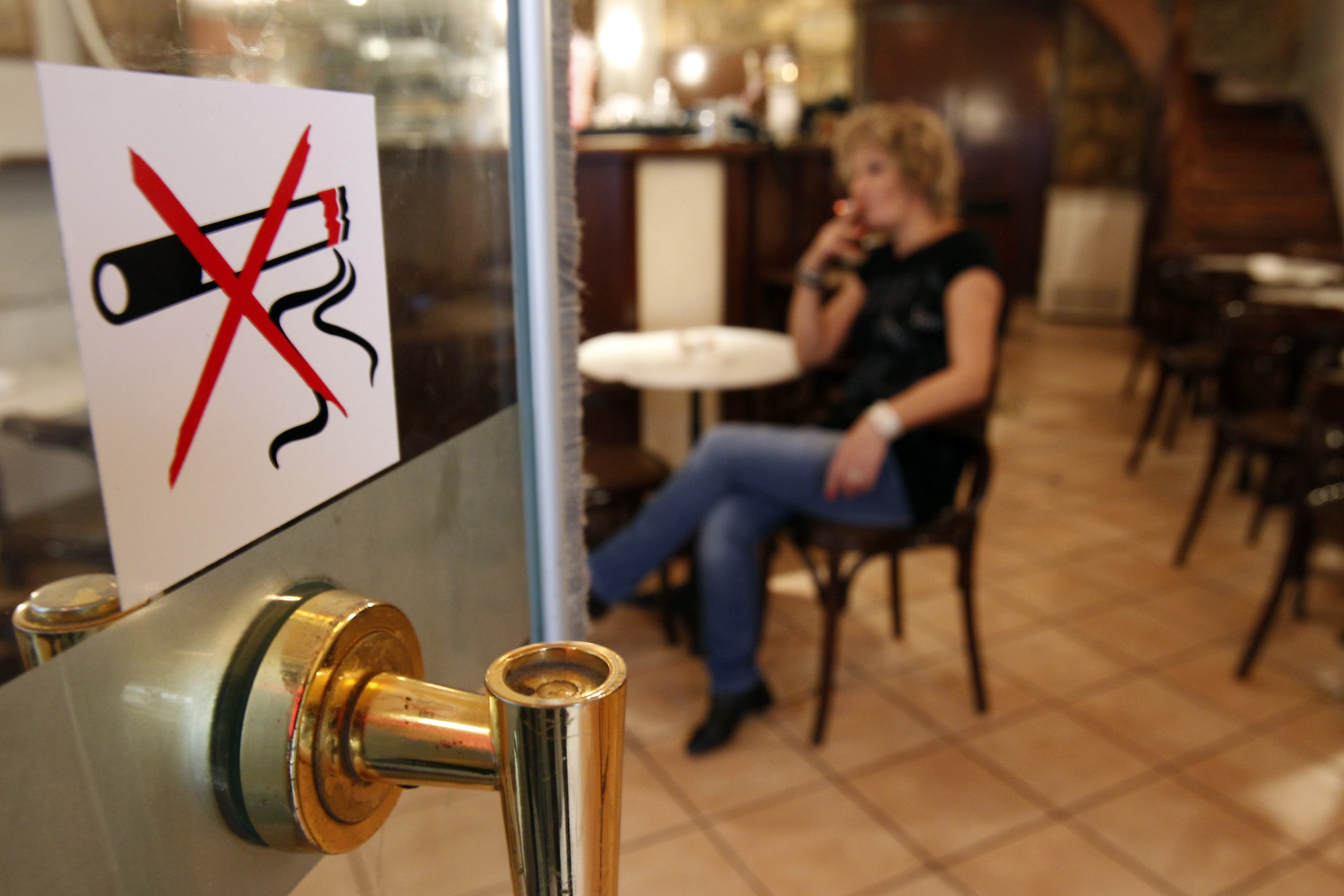 A woman smokes a cigarette behind a smoking ban sign in a restaurant-cafe in central Athens October 18, 2010. Businesses around Greece have decided to violate a smoking ban and have placed ashtrays back on tables and allow customers to smoke inside, despite the law and heavy fines, saying an economic crisis and smoking ban simultaneously is killing business. REUTERS/John Kolesidis (Greece - Tags: POLITICS SOCIETY)