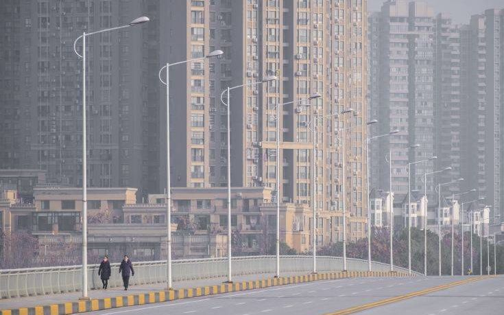 People wearing face masks walk down a deserted street in Wuhan in central China's Hubei Province, Tuesday, Jan. 28, 2020. China's death toll from a new viral disease that is causing a  global concern rose by 25 to at least 106 on Tuesday as the United States and other governments prepared to fly their citizens out of the locked-down city at center of the outbreak. (AP Photo/Arek Rataj)