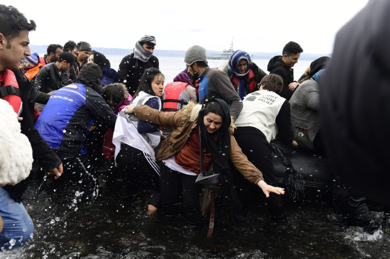 """Migrants arrive with a dinghy at the village of Skala Sikaminias, on the Greek island of Lesbos, after crossing the Aegean sea from Turkey, on Friday, Feb. 28, 2020. NATO envoys held emergency talks at the request of Turkey, a NATO member, and scores of migrants began converging on Turkey's border with Greece seeking entry into Europe after Turkey said it was """"no longer able to hold refugees."""" (AP Photo/Michael Varaklas)"""