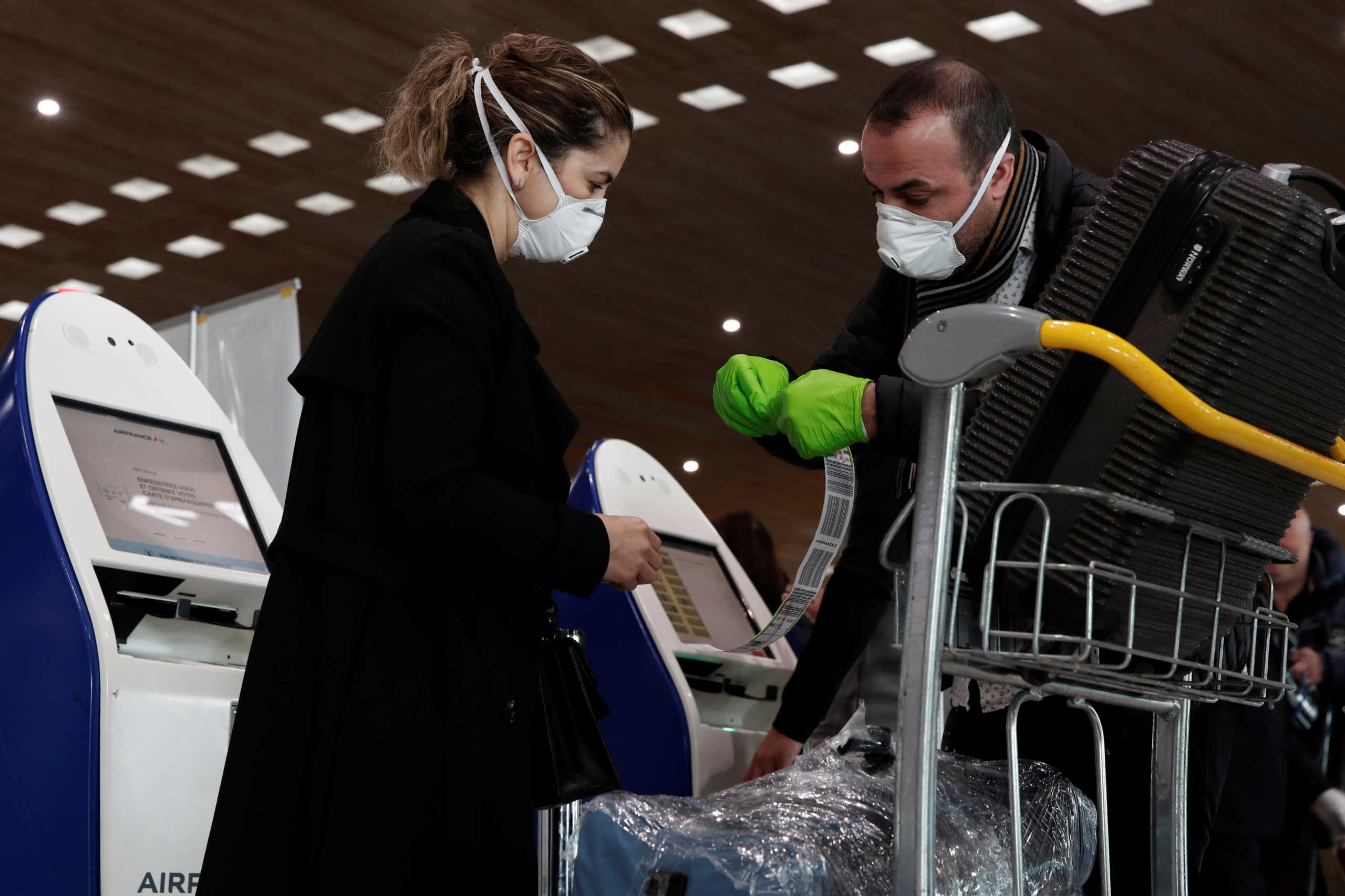 People wearing protective face masks and gloves check in luggage at the Air France desks inside Terminal 2E at Paris Charles de Gaulle airport in Roissy, after the U.S. banned travel from Europe, as France grapples with an outbreak of coronavirus disease (COVID-19), March 12, 2020.  REUTERS/Benoit Tessier