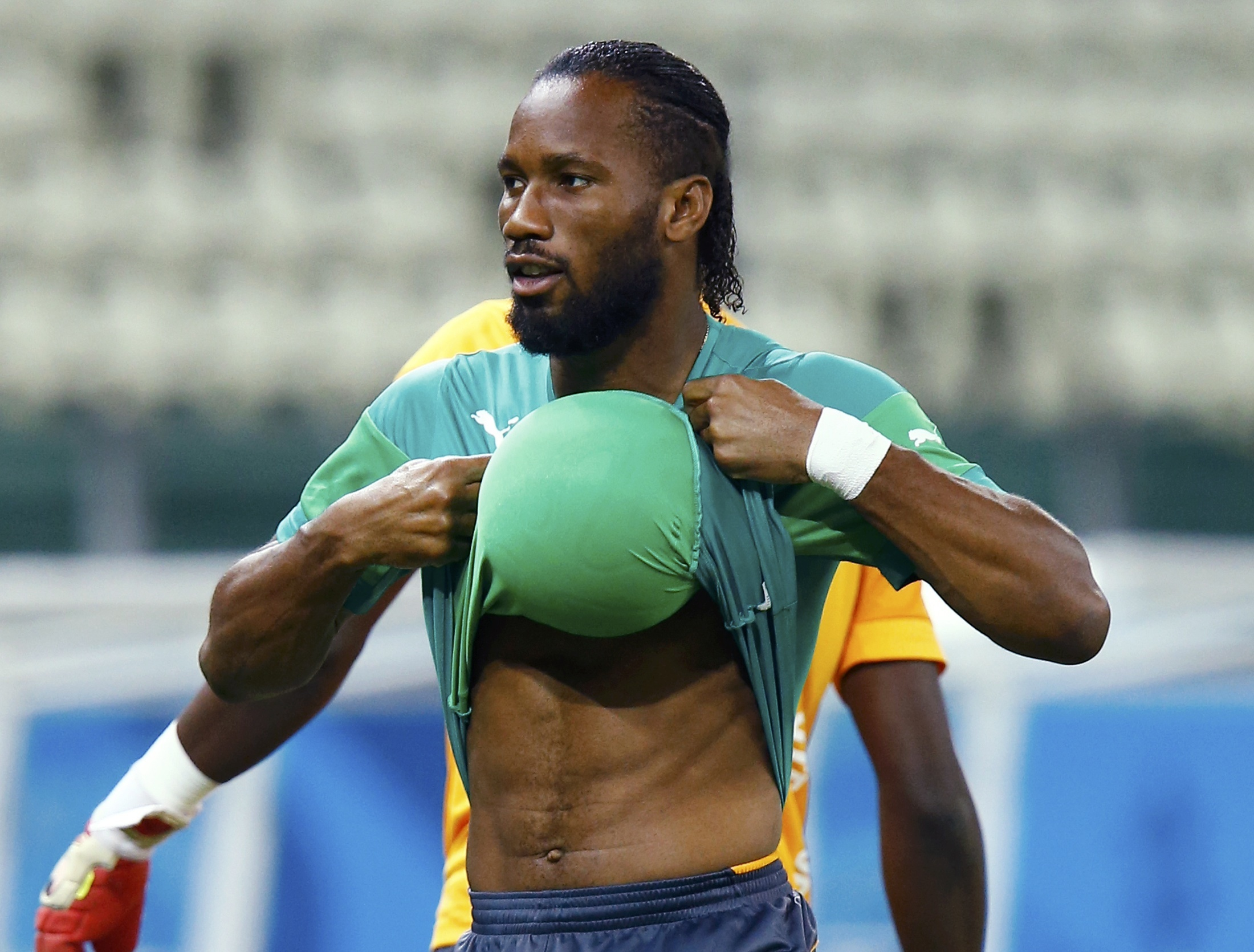 Ivory Coast national team forward Didier Drogba hides a ball under his shirt during practice at Castelo Stadium in Fortaleza June 23, 2014.   REUTERS/Mike Blake (BRAZIL  - Tags: SPORT WORLD CUP SOCCER)