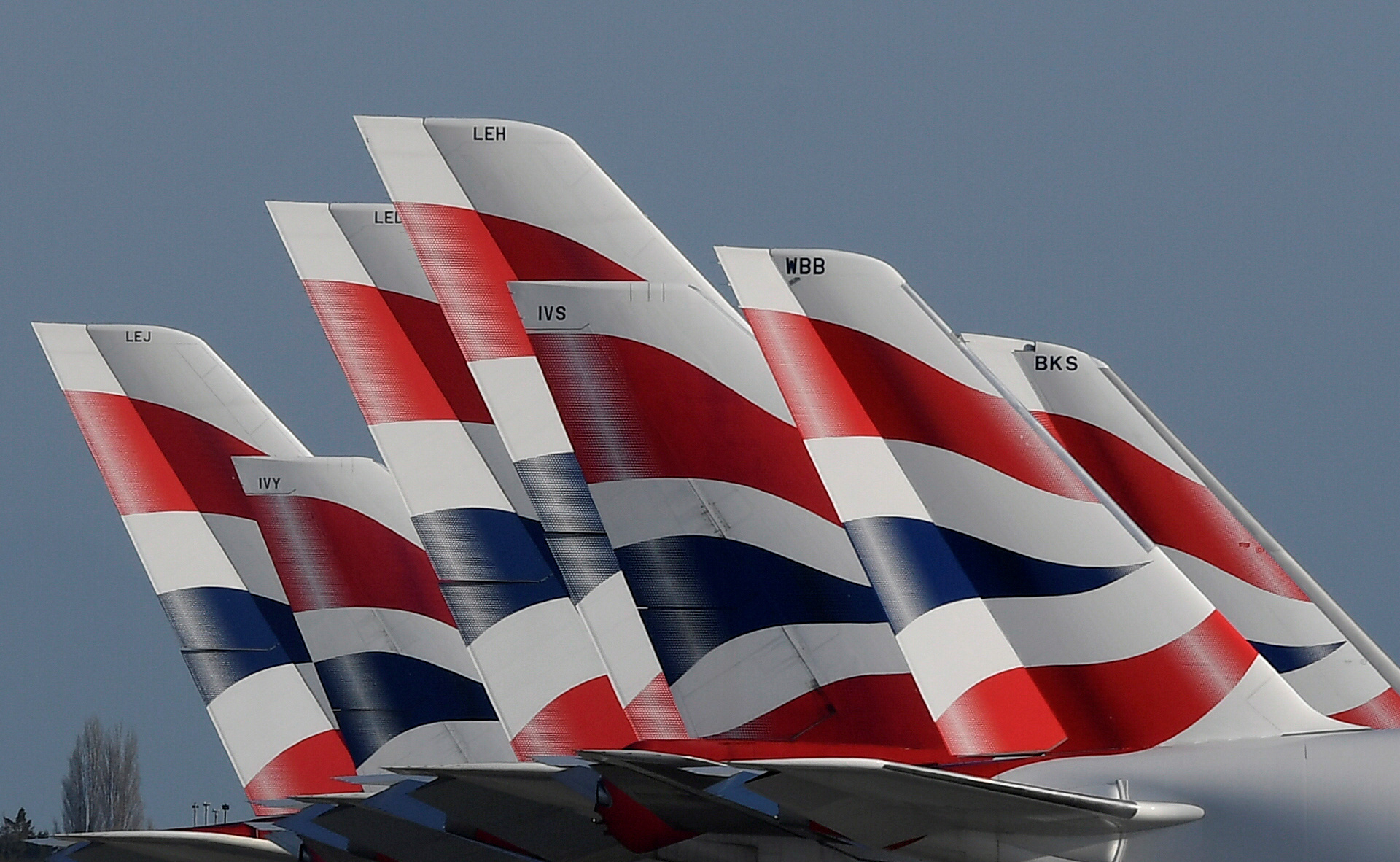 FILE PHOTO: Tail Fins of British Airways planes are seen parked at Heathrow airport as the spread of the coronavirus disease (COVID-19) continues, London, Britain, March 31, 2020. REUTERS/Toby Melville/File Photo