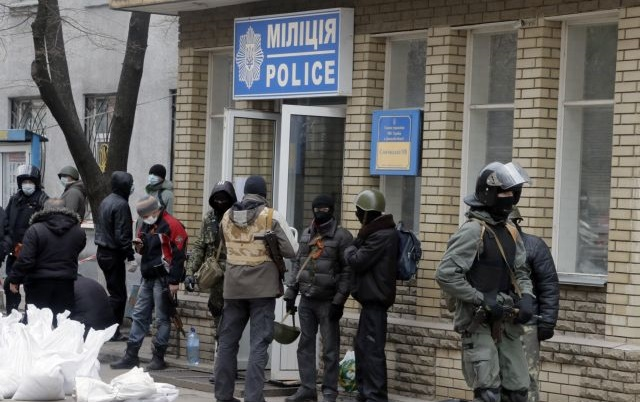 Armed pro-Russian activists occupying the police station in the eastern Ukraine town of Slavyansk carry riot shields on in Slavyansk, Saturday, April 12, 2014. Pro-Moscow protesters have seized a number of government buildings in the east over the past week, undermining the authority of the interim government in the capital, Kiev. (AP Photo/Efrem Lukatsky)