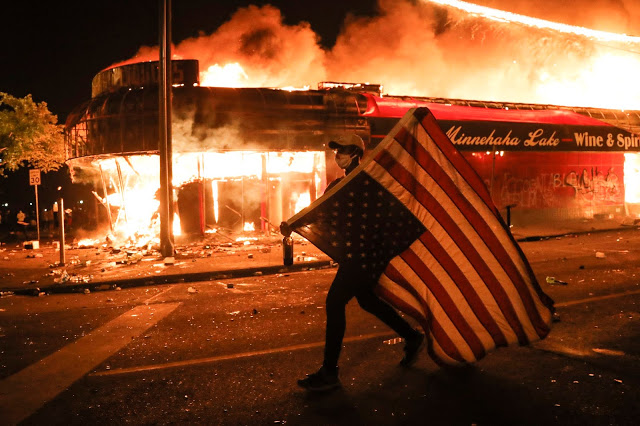A protester carries a U.S. flag upside, a sign of distress, next to a burning building, early Friday, May 29, 2020, in Minneapolis. Protests over the death of George Floyd, a black man who died in police custody Monday, broke out in Minneapolis for a third straight night. (AP Photo/Julio Cortez)