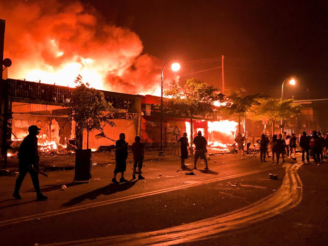 Flames rise from a liquor store and shops near the 3rd Police Precinct in Minneapolis on Thursday, during a protest over the death of George Floyd.