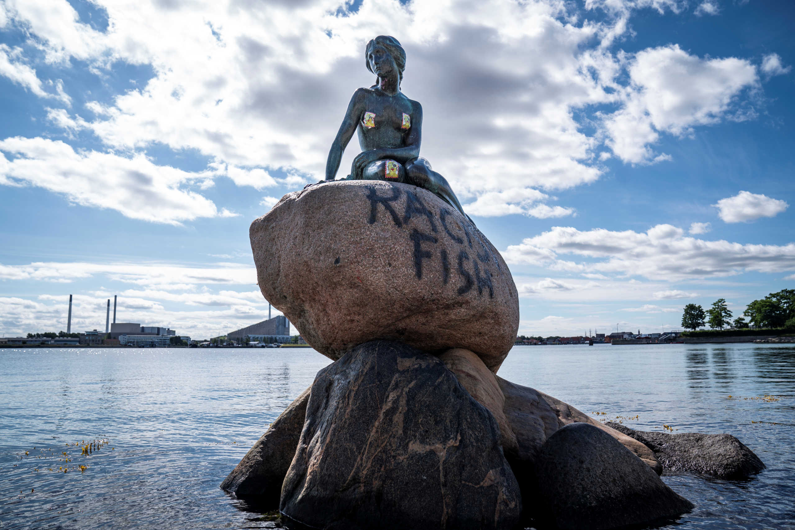 """A graffiti reading """"Racist Fish"""" is seen on a statue of """"The Little Mermaid"""" in Copenhagen, Denmark July 3, 2020. Ritzau Scanpix/Niels Christian Vilmann via REUTERS    ATTENTION EDITORS - THIS IMAGE WAS PROVIDED BY A THIRD PARTY. DENMARK OUT. NO COMMERCIAL OR EDITORIAL SALES IN DENMARK."""