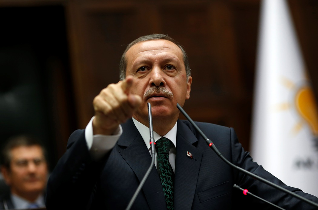 Turkey's Prime Minister Tayyip Erdogan addresses members of parliament from his ruling AK Party (AKP) during a meeting at the Turkish parliament in Ankara June 25, 2013. Turkish anti-terrorism police detained 20 people in raids in the capital Ankara on Tuesday in connection with weeks of anti-government protests across the country, media reports said. The unrest began at the end of May when police used force against campaigners opposed to plans to redevelop a central Istanbul park. The protest spiralled into broader demonstrations against Prime Minister Tayyip Erdogan and his government. REUTERS/Umit Bektas (TURKEY - Tags: POLITICS) - RTX1102A
