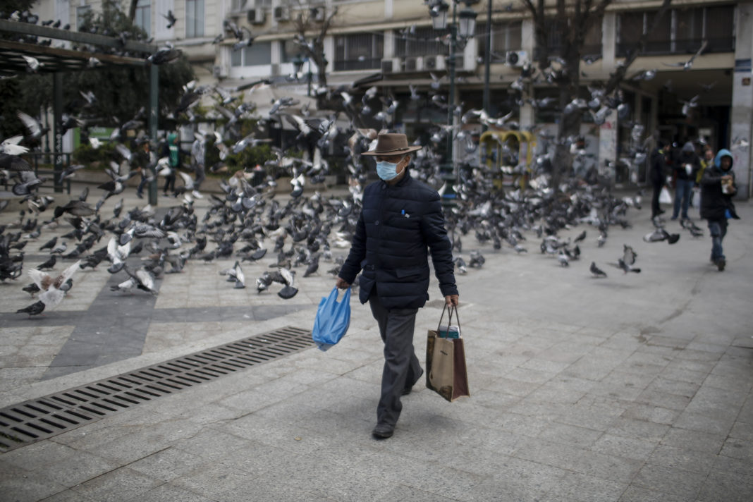epa08298620 An elderly man wearing a protective mask and carrying shopping bags walks in Athens, Greece, 16 March 2020. The total number of confirmed infections of COVID-19 in Greece is 352, said the Health Ministry?s coronavirus spokesman and infectious diseases Professor Sotiris Tsiodras at the daily briefing to reporter, with 65 of these patients hospitalized.  EPA-EFE/KOSTAS TSIRONIS
